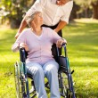 Middle aged son taking his disabled mother for a walk — Stock Photo