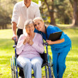 Stock Photo: Caring nurse hugging senior patient