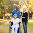 Middle aged couple taking disabled mother for a walk — Stock Photo