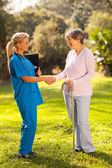 Female nurse greeting recovering senior patient — Stock Photo