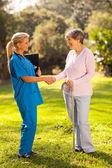 Female nurse greeting recovering senior patient — Stock Photo