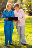 Nurse showing senior patient medical test results — Stock Photo
