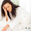 Woman sitting on bed and having headache — Stock Photo #29434963