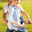 Senior couple on a bicycle outdoors — Foto de Stock