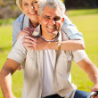 Mid age couple on one bike outdoors — Stock Photo