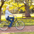 Mature woman riding a bike at the park — Stockfoto