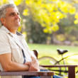 Middle aged man sitting at the park — Stock Photo
