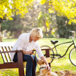 Middle aged woman playing with pet dog at the park — Stock Photo