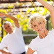 Senior woman exercising with husband outdoors — Stock Photo