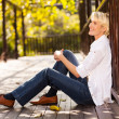 Happy mid age woman sitting outdoors — Stockfoto