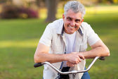 Middle aged man on a bike — Stock Photo