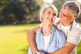 Middle aged couple embracing outdoors — Stock Photo