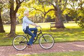 Mujer madura montando una bicicleta en el parque — Foto de Stock
