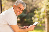 Middle aged man holding tablet computer outdoors — Stock Photo