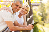 Senior couple with tablet computer outdoors — Stock Photo