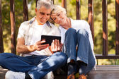 Senior couple using tablet computer outdoors — Stock Photo