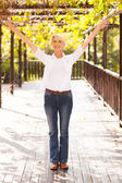 Mid age woman with arms outstretched — Stockfoto
