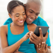 Foto Stock: Africamericmarried couple using tablet computer