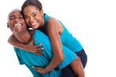 African woman enjoying piggyback ride on boyfriends back — Stock Photo