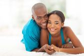 Loving young african couple lying on bed — Stock Photo