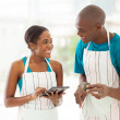 African couple searching for a recipe — Stock Photo