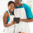 African couple using the internet to look up for a recipe — Stock Photo