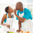 Stock Photo: African husband feeding wife a piece of tomato