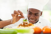 Afro American chef in restaurant kitchen garnishing pasta dish — Stock Photo
