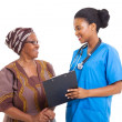 Young africnurse helping senior womwith medical form — Stock Photo #30765353