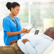 Stock Photo: Africfemale doctor consulting senior patient