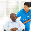 Stock Photo: African nurse taking care of senior patient in wheelchair