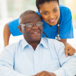Photo: Elderly africamericmand caring young caregiver