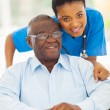 Stock Photo: Elderly africamericmand caring young caregiver