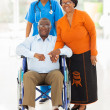 Stock Photo: African female healthcare worker with senior couple