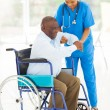 African caregiver helping senior man getting up — Stock Photo