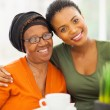图库照片: Senior african woman with daughter at home