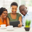 young adult african girl with senior parents using tablet comput — Stock Photo