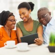 Stock Photo: African family at home using tablet pc