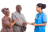 Friendly african nurse hand shake with senior patient and wife — Stock Photo