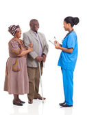 Young african medical nurse and elderly couple patient — Stock Photo