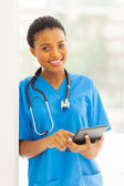 Young african nurse using tablet pc — Stock Photo