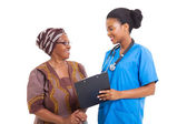Young african nurse helping senior woman with medical form — Stock Photo