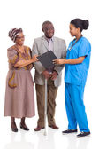 Young african nurse talking to senior couple — Stock Photo