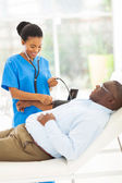 Doctor checking senior patient's blood pressure — Stockfoto