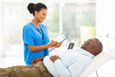 African female doctor consulting senior patient — Stock Photo