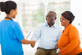 African female nurse greeting senior couple — Stock Photo