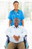 Ganska afrikanska hälso-och arbetaren och funktionshindrade äldre patient — Stockfoto