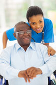 Elderly african american man and caring young caregiver — Stok fotoğraf