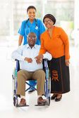 African female healthcare worker with senior couple — Stock Photo