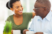 Elderly african american man enjoying coffee with his granddaugh — Stock Photo